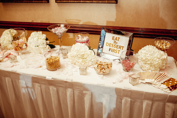 Candy bar. Different kinds of sweets stand on the table during a wedding dinner. Lettering 'Eat the Dessert first' stands on the table