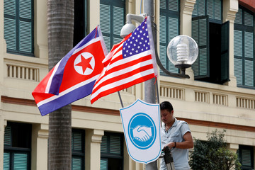 A man places North Korean and U.S. flags in the street ahead of the summit in Hanoi