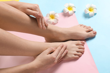 Wall Murals Pedicure Legs and hands of young woman with beautiful pedicure and manicure on color background