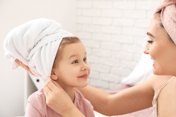 Cute little daughter with her mother after shower at home