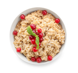 Bowl with tasty oatmeal on white background