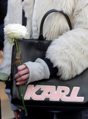 A woman holds a white rose as she stands outside the Chanel fashion boutique after news that German haute-couture designer Karl Lagerfeld, artistic director at Chanel and an icon of the global fashion industry for over half a century, has died, aged 85, i