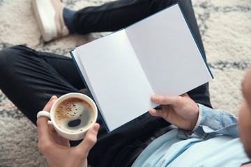 Young man drinking coffee while reading book at home