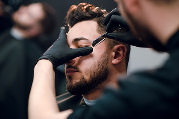 Young attractive brunette man is getting shaved with a vintage razor by a hairdresser at the barbershop. Beard haircut.