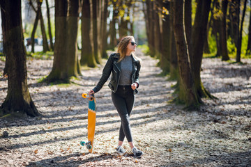 Young beautiful woman in stylish outfit and black sunglasses walking with longboard in the autumn park. Sunny day