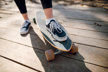 Close up of skateboarder legs on the longboard. Woman i black sneakers riding skateboard outdoor on the wooden surface at park. Sunny day