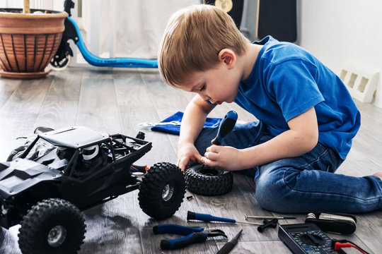 Auto modeling: little boy repairing a model radio-controlled car at home.