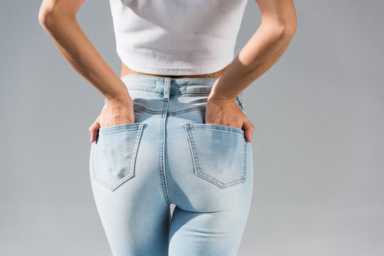 Cropped view of young woman in jeans with hands in pockets isolated on grey