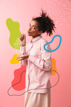 Beautiful young african woman posing isolated over pink wall background imagine that she drinking tea.