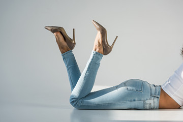 Cropped view of woman in jeans and high-heeled shoes on grey background
