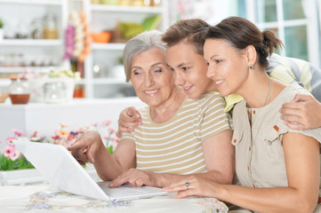 Smiling grandmother,  mother and son using laptop