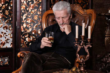 Portrait of senior man drinking at home