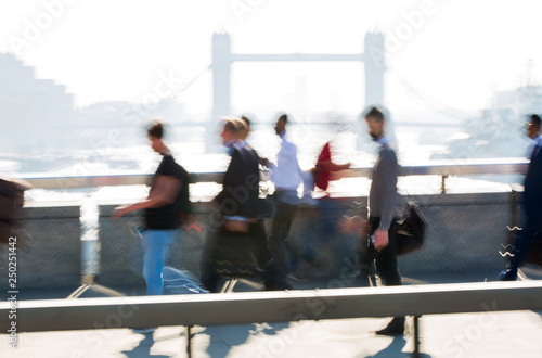 Blur of people walking over the London bridge on the way to
