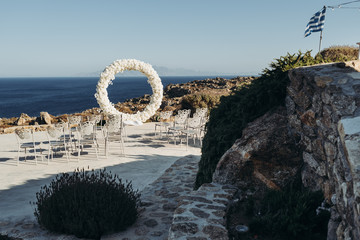 Wedding decor. Round arch made of while flowers stands on the shore with great seaview behind