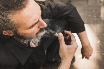 Bearded brutal man smoking pipe