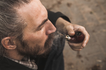 Brutal bearded man smoking pipe