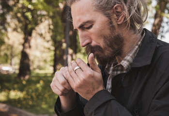 Serious bearded man lights his pipe