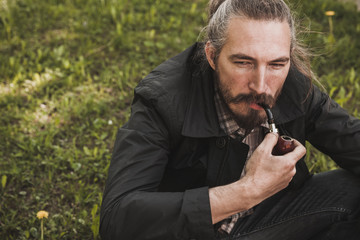Serious bearded man smoking pipe