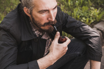 Brutal bearded man with pipe
