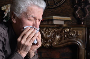 Portrait of sick senior man with handkerchief