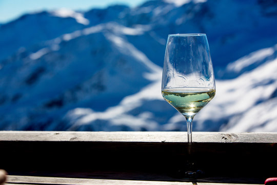 Glass of wine, sitting on rim on a deck, winter landschape behind
