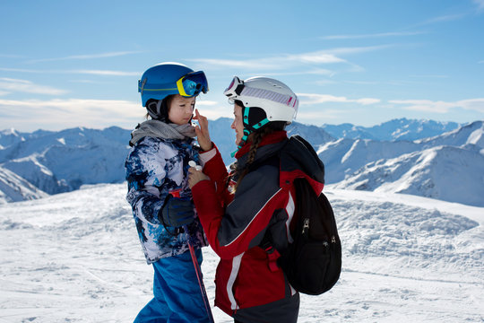Parent, mother, putting sun cream on child's face on top of mountain