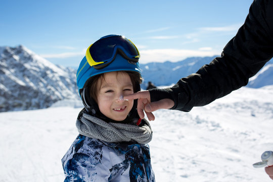 Parent, father, putting sun cream on child's face on top of mountain