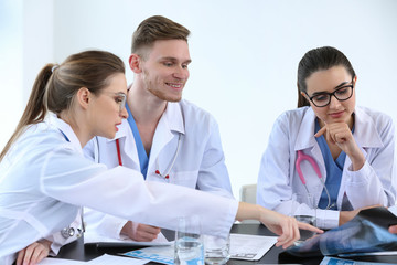 Team of doctors discussing diagnosis at table in clinic