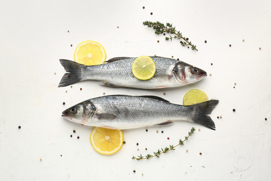 Tasty fresh seabass fish with spices on white background