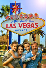 Portrait of happy family posing against Las Vegas sign