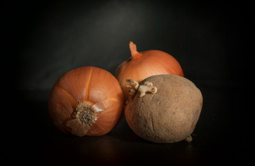 potatoes and two onions on a black background on a black surface