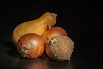 potatoes with sprouts in the foreground onions and pumpkins on a black background