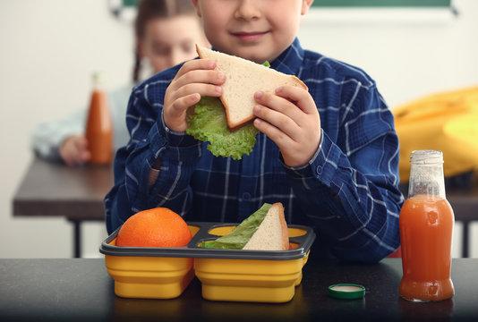 Little boy having school lunch in classroom