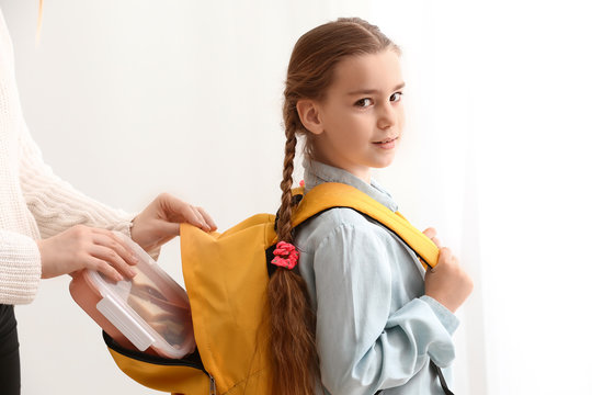 Mother putting lunch box into backpack of her little daughter before school