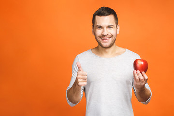 Cheerful beautiful man eating apple, isolated over orange background. Thumbs up.