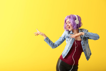 Beautiful young woman with headphones dancing against color background