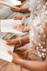Three women in sparkling dresses sit with books on the chairs