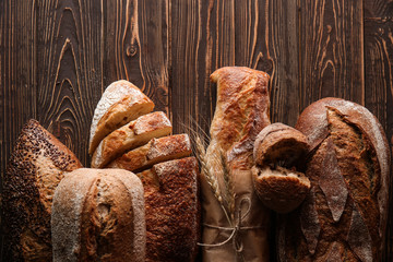 Different fresh bread on wooden background