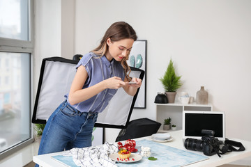 Female food photographer with mobile phone taking picture of tasty cake in home studio