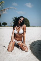 Young happy woman in white bikini on the beach