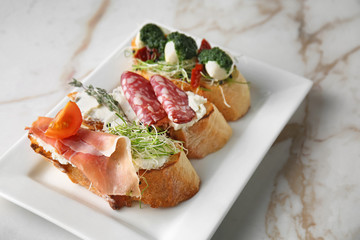 Plate with fresh tasty bruschettas on light background