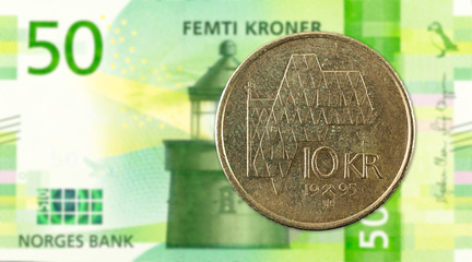 10 norwegian krone coin against 50 new norwegian krone banknote