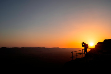 Photographer who shoots a sunset in the mountains