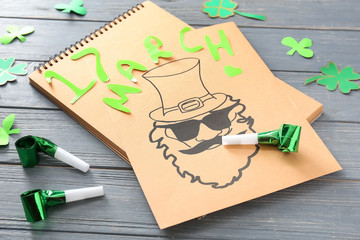 Paper sheet with drawing of leprechaun and party decor on wooden table. St. Patrick's Day celebration
