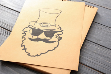 Paper with drawing of leprechaun on wooden table. St. Patrick's Day celebration