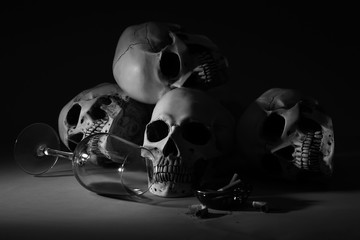 Human skulls, alcohol and cigarettes on black background. Concept of addiction
