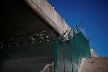 Razor wired security fence preventing migrants from climbing is seen under the main motorway next to the Calais Port
