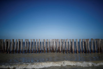 Wooden posts, to fight sea erosion, protude from the beach Oye-Plage beach, near Calais
