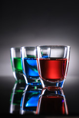 Three Colorful Shot Glasses on Grey Background