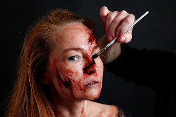 Cinema make-up artist Michael Loncin uses a paintbrush to give model fake wounds at FX Bubbles studio, specialised in gory cinema make-up, in Brussels